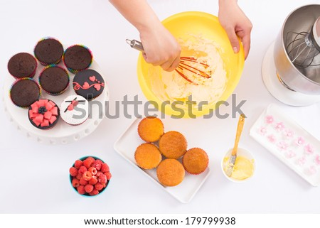 Below view of a table where human hands whisking dough for cake with a silicone beater, prepared fancy cakes and raspberry are nearby  - stock photo