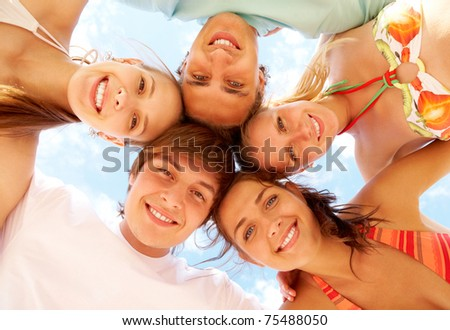 Below view of joyful teens embracing and looking at camera with smiles