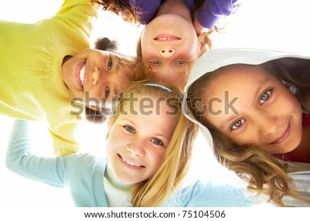 Below view of several happy girls standing head by head to each other