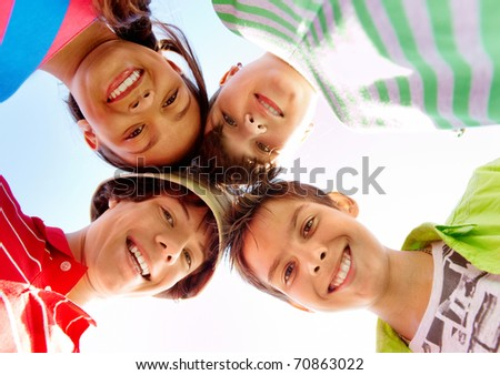 Below view of several happy teens standing head by head to each other