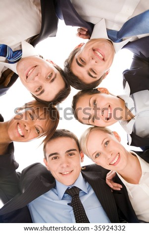 Below view of several smart colleagues looking at camera with smiles