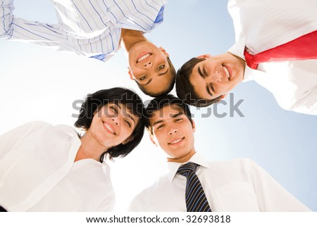 Below view of several successful partners looking at camera with happy smiles