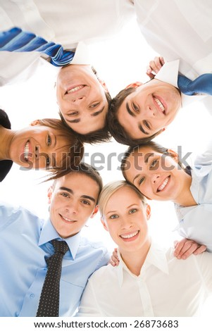 Below view of several successful partners looking at camera with smiles