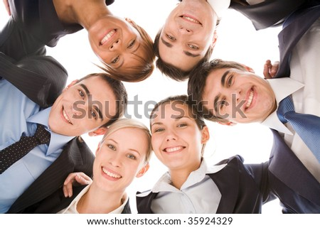 Below view of several successful partners looking at camera with smiles - stock photo
