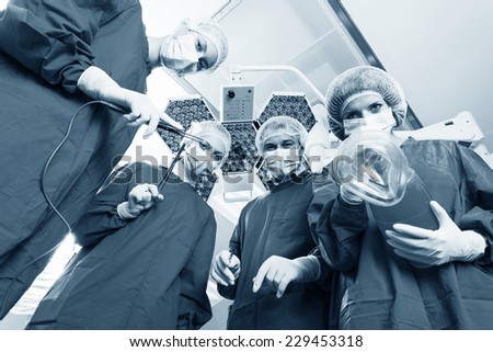 Below view of surgeons holding medical instruments in hands and looking at patient - stock photo