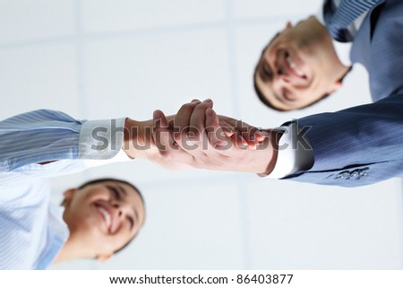Below view of two handshaking partners - stock photo
