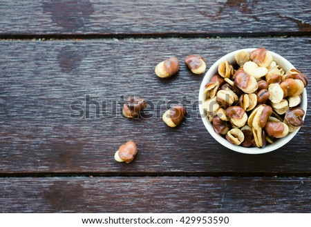 belted broad bean in the white bowl on wooden background.Nuts Concept.Broad bean. - stock photo