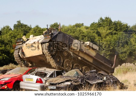 BELTRING, UK - AUGUST 14: An ex British army FV432 APC drives over a line of parked cars demonstrating both its agility and weight at the Military World show on August 14, 2016 in Beltring