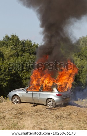 BELTRING, UK - AUGUST 14: An old car is set fire to with pyrotechnic gunfire during a tank demonstration to the watching public at the Military World show on August 14, 2016 in Beltring