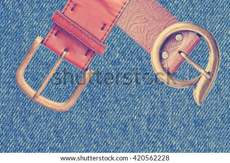 Belts with buckle unit on denim ( jeans) fabric texture background. Toned colors vintage image - stock photo