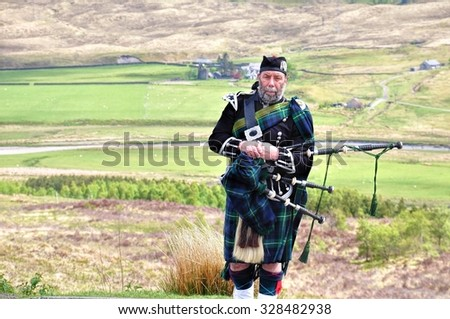 BEN NEVIS, SCOTLAND - JUNE 2, 2013: Scottish Bagpiper  with a  bagpipe. - stock photo