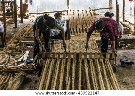 BEN TRE, VIETNAM - JUNE 19, 2016 - Vietnamese female spin coconut fiber to make material for coir mat, a tradition product from coconut at spinning coir traditional village, Bentre, Vietnam