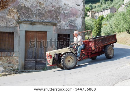 Benabbio, Italy-June 4, 2015. Local villager drving a tractor through the narrow and winding streets of Benabbio, Italy - stock photo