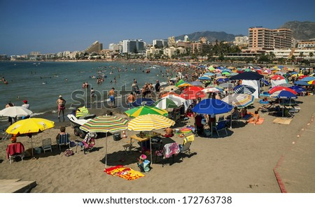 BENALMADENA - JULY 20: A crowd of vacationers enjoy the warm beaches of Costa del sol on JULY 20, 2013 in Benalmadena, Spain. - stock photo