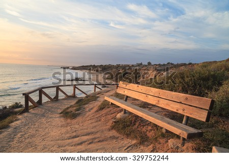 Bench along an outlook with a view of Crystal Cove Beach, Newport Beach and Laguna Beach line in Southern California - stock photo