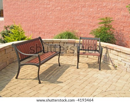 Bench and chair sitting on a patio of a commercial site; sitting walls, plantings etc.
