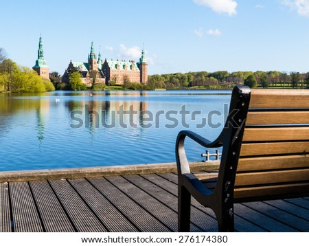 Bench and mooring against view on the Palace - Frederiksborg Slot, Hillerod, Denmark - stock photo