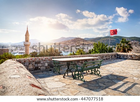 Bench and table on the roof on the Bodrum Castle museum near Aegean Sea with yachts at sunset - stock photo
