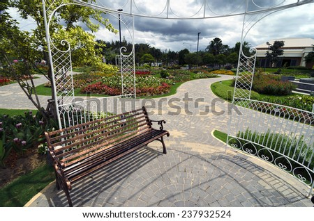 Bench in a garden with flowers and arbor - nice and neat outdoor park