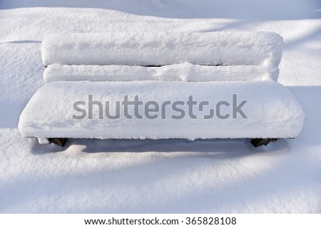 Bench in a park covered completely by snow after heavy snowfall - stock photo