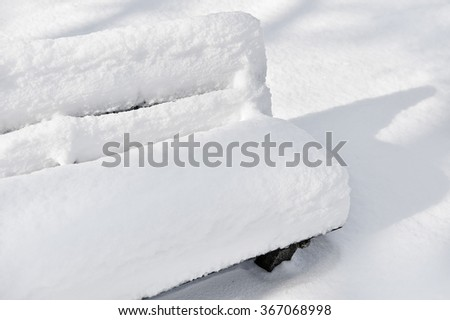 Bench in a park covered completely by snow after heavy snowfall