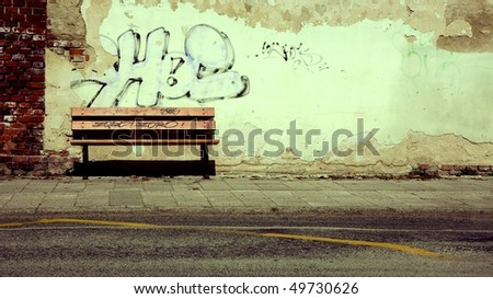 Bench in front of rusty wall