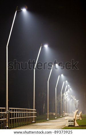 Bench in night alley with lights - stock photo
