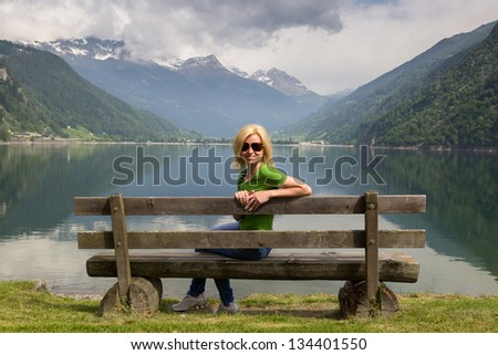 bench in the high mountains at the lake Poschiavo, Switzerland Alps - stock photo