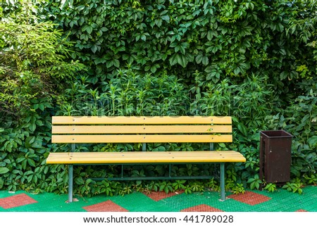 Bench in the park on a background of vegetation with the trash. Bench on the protective coating - stock photo