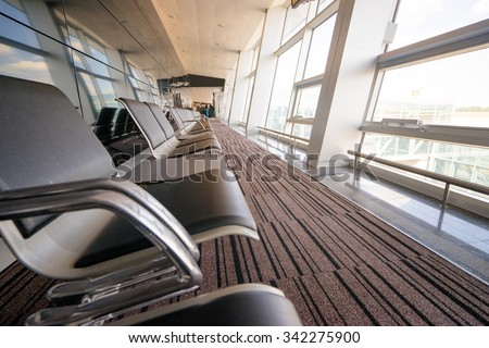 Bench in the terminal of airport. Empty airport terminal waiting boarding area with chairs. - stock photo