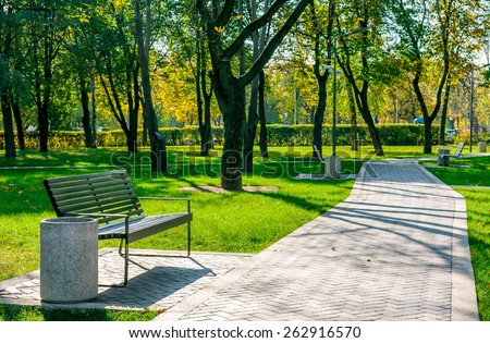 bench near the path of paving stones in a quiet city park early autumn on a sunny day on a background of trees - stock photo
