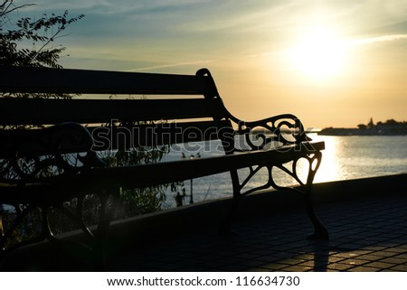 Bench near the sea against beautiful sunset - stock photo