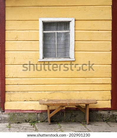 bench near the wooden wall with window of old house - stock photo