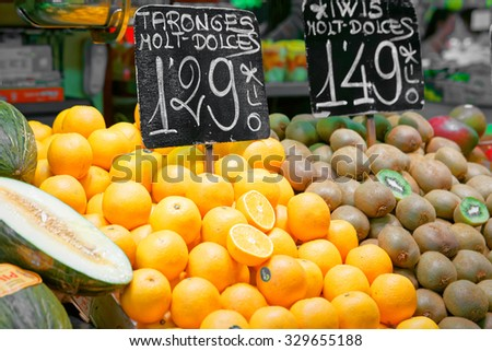 Bench of oranges and kiwi in a spanish market with a price list