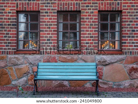 Bench on a background of a brick wall with windows - stock photo
