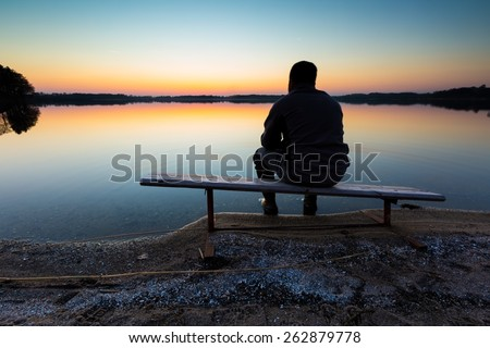 Bench on lake shore at sunset. Beautiful landscape with one man sitting and looking on sunset. Photographed in Poland. - stock photo