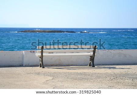 Bench on the coast of Aegean Sea in Malia, Crete, Greece. - stock photo