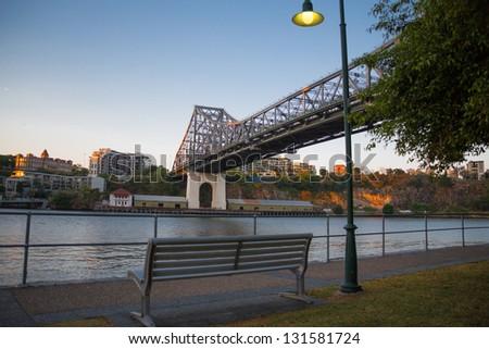Bench on the footpath under storey bridge, Brisbane, Australia - stock photo