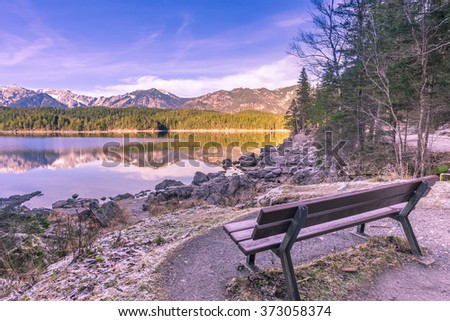 Bench on the shore of an alpine lake - Winter image with a bench located on the shore of the Eibsee lake, from Grainau, Germany. Reflected in its water are the Bavarian Alps mountains. - stock photo