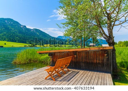 Bench on wooden jetty in alpine village on shore of Weissensee lake in summer landscape of Alps Mountains, Austria - stock photo