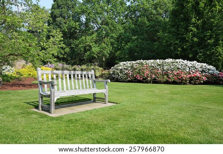 Bench seat in an english park with flowering rhododendrons - stock photo
