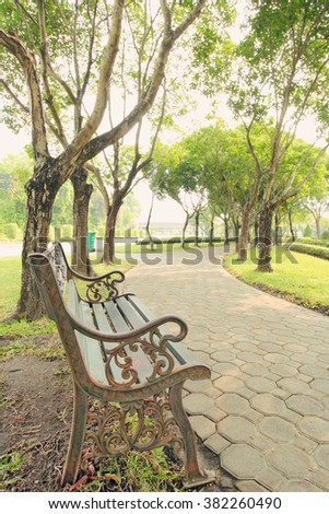 Bench under the tree in the Gardens - stock photo