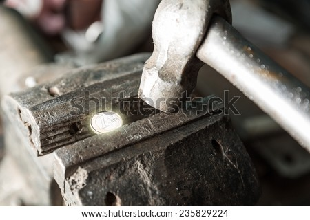 Bench vice with 1 euro coin and a hammer - stock photo