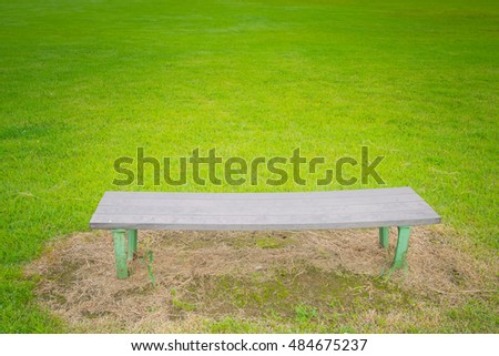 Bench with green field in plubic garden
