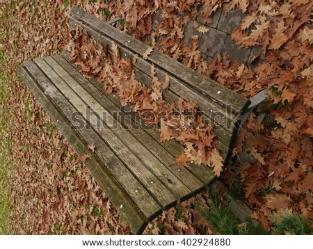 bench with leafes in autumn - stock photo