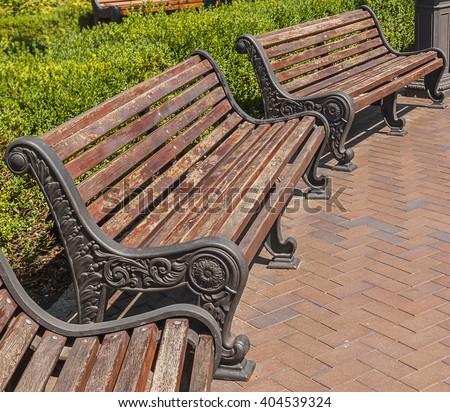 Benches in a public garden a bright summer day - stock photo