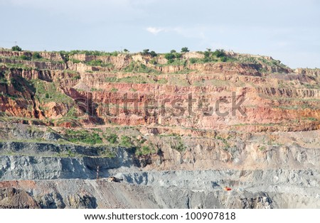 Benches in opencast coal mine - stock photo