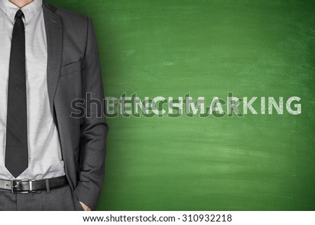 Benchmarking text on green blackboard with businessman - stock photo