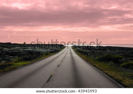 Bend in the road leads to a gorgeous pink sunset.  Life has been full of rocks and quite bare.  Bend can lead to a new beginning.  This sunset is in Volcanoes National Park,Big Island,Hawaii. - stock photo
