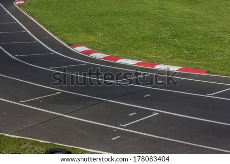 Bend of a tarmac racetrack with white lines - stock photo
